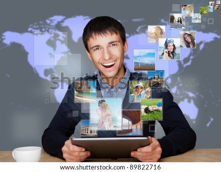 A technology man has images flying away from his modern tablet computer. Designed poster for a communication, social media sharing or tv concept. - stock photo