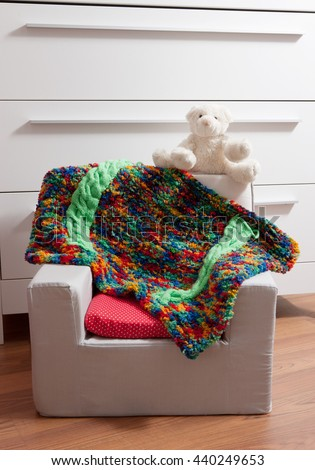 a teddy bear on a small armchair with a quilt - stock photo