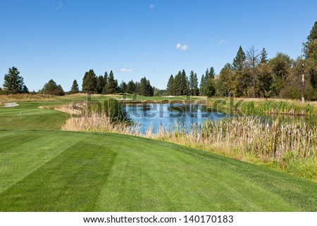 A tee off area looking down course over a pond and to the hole by the tree line at a North Idaho golf course on a sunny day. - stock photo