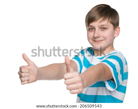A teen boy holds his thumbs up on the white background - stock photo