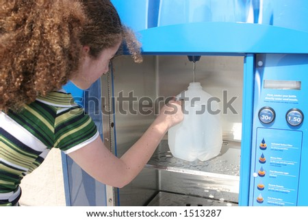 A teen girl filling a water bottle at a vending machine in preparation for a hurricane.  Could also be used for recycling. (focus on hand & water bottle) - stock photo