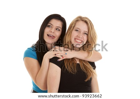 a teen girl having some fun while giving her friend a hug. - stock photo