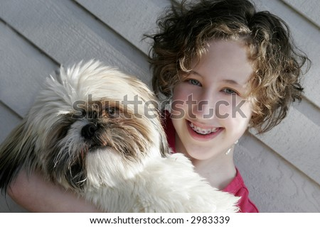 A teen girl holding her dog - stock photo