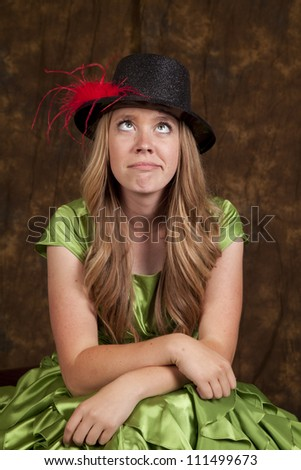 a teen girl showing a funny expression by looking up at a top hat on her head. - stock photo