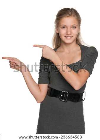 A teen girl shows her fingers to the side against the white background - stock photo