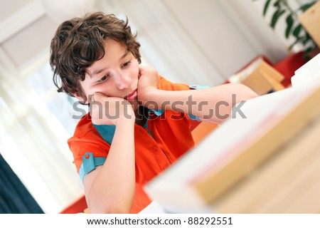 A teen school boy studies hard over his books at home as he props his head up with his arms. - stock photo