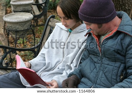 A teen volunteer reading the bible to a homeless person. Focus on the teen's face - stock photo