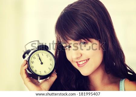 A teen woman with alarm clock - stock photo