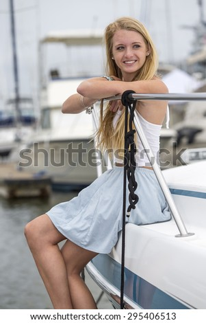 A teenage blonde model posing outdoors with boats - stock photo