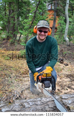 A teenage boy cutting a tree with a chain saw in a forest - stock photo