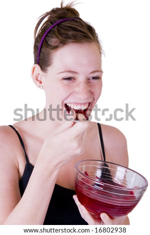 A teenage girl eating red jello or jelly. Isolated on a white background. - stock photo