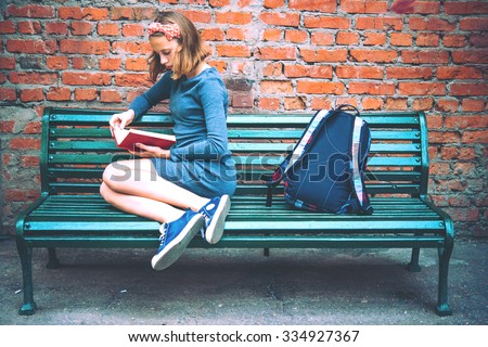 A teenage girl is reading on a bench with brick wall in the background. Toned image - stock photo