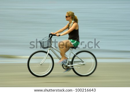 A teenage girl on a beach riding a bike. Panned to show motion. - stock photo