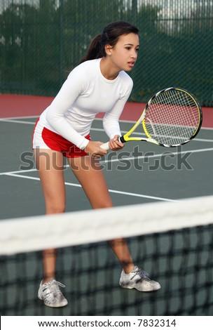 A teenage girl playing tennis - stock photo
