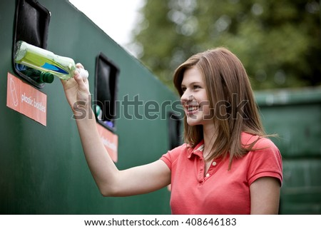 A teenage girl recycling a plastic bottle, smiling - stock photo