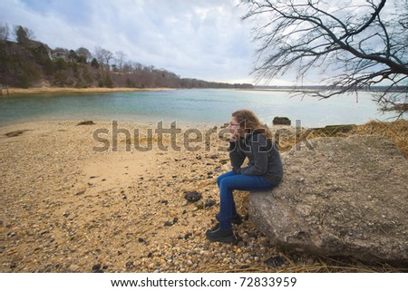 A teenage girl sitting quietly, looking out into the water on a cloudy day - stock photo