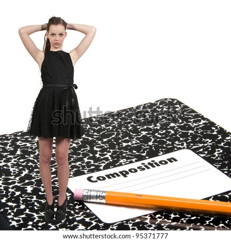 A teenage girl with a number 2 pencil and a composition book. - stock photo