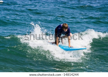 A teenager surfing. The boy is just beginning to stand up on the surfboard. - stock photo
