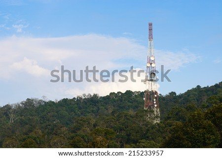 A telecommunications tower on a forest - stock photo