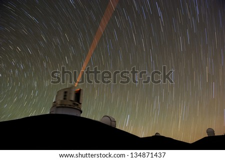 A telescope using a red laser guide star. Long exposure photograph from the summit of Mauna Kea, Hawaii. - stock photo