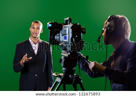 A television presenter in a TV studio with a camera and operator out of focus in the foreground and a green screen in the background. Some motion blur on the presenter's head and hands. - stock photo