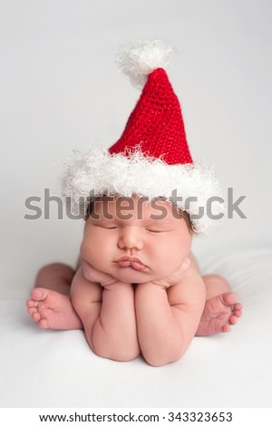 A ten day old, newborn, baby girl wearing a crocheted Santa hat. She is posed with her hands under her chin and sleeping on a white fabric backdrop.  - stock photo