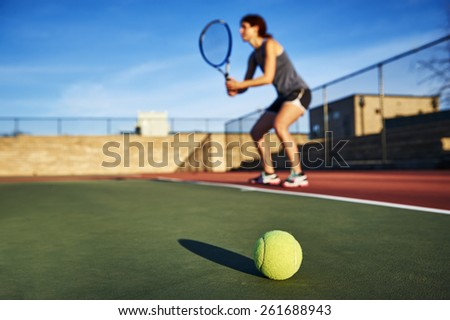 a tennis ball and young woman holding a tennis racquet in background.  focus on tennis ball. - stock photo
