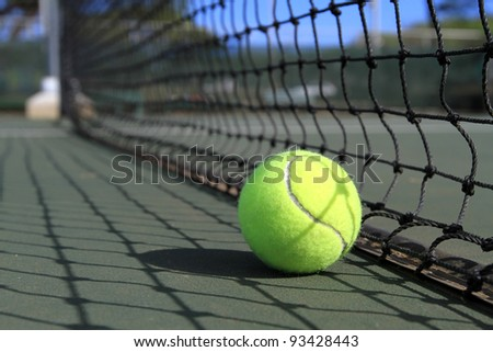 A tennis ball lies on the court next to the net in broad sunny daylight - stock photo