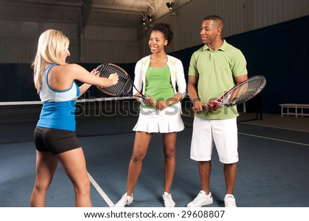 a tennis instructor giving a lesson to a couple - stock photo