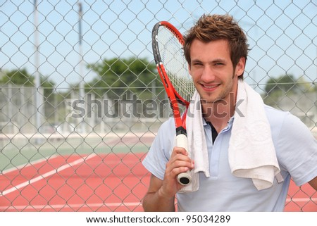A tennis player posing in front of a tennis court with his racket. - stock photo