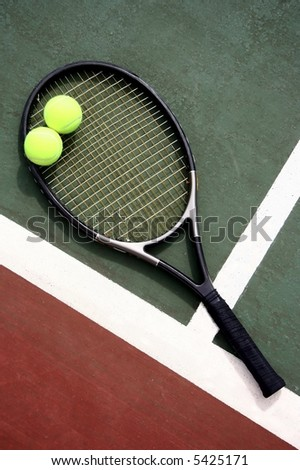 A tennis racket and two balls on a tennis court - stock photo