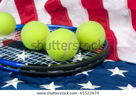 A tennis racket with new tennis balls on an American flag - stock photo