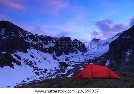 A tent in the Alps during an beautiful evening. - stock photo