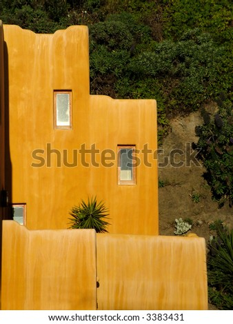 A terracotta colored house with a Mexican design - stock photo