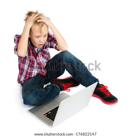 A terrified pre-teen boy with tousled hair sitting in front of  a laptop computer, looking at its screen with awe and terror - stock photo