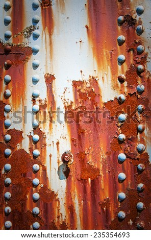 A textured grungy background image of rusted plate metal and rivets. - stock photo