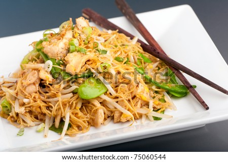 A Thai dish of chicken and noodles stir fry presented on a square white plate with wooden chopsticks. - stock photo