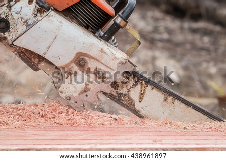 A Thai worker cutting trunk with chainsaw - stock photo