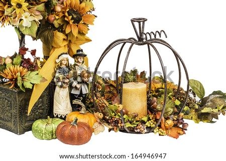 A Thanksgiving and Fall arrangement showing flowers, pumpkins, pilgrims and a candle. - stock photo