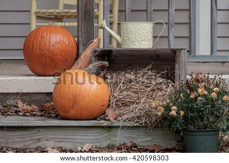 A Thanksgiving Holiday decorated porch with pumpkins and hay - stock photo