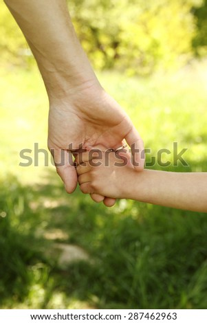 a the parent holding the hand of a small child - stock photo