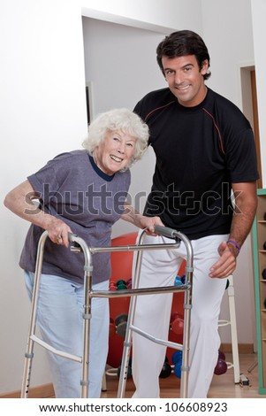 A therapist assisting a senior woman onto her walker. - stock photo