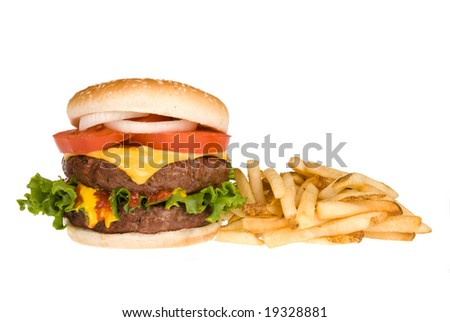 A thick, fresh, juicy hamburger with all the trimmings rests next to a pile of salty French fries.  Image isolated on white for use in any promotional inferences. - stock photo