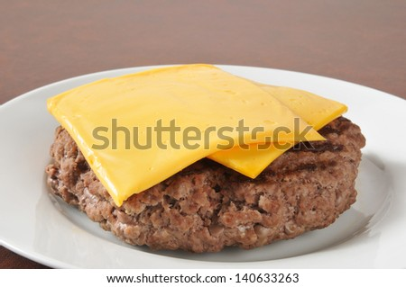A thick hamburger patty with slices of American or Cheddar cheese - stock photo