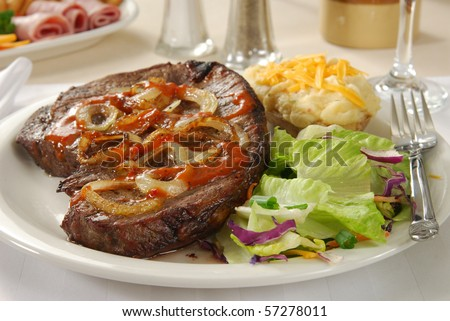 A thick steak served with sauteed onions, salad and twice baked potato - stock photo