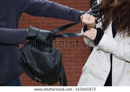 A thief stealing a black leather backpack - stock photo