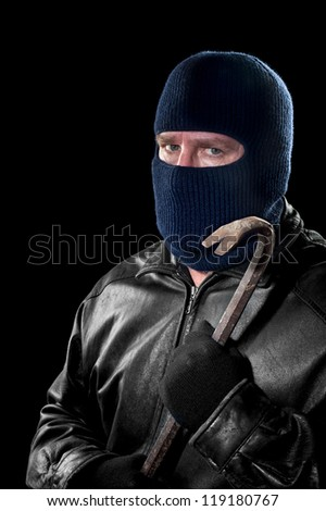 A thief wearing a ski mask to hide his identity holds a crowbar and prepares to commit a crime. - stock photo