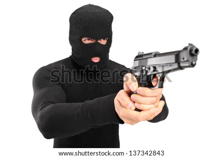 A thief with robbery mask holding a gun isolated against white background - stock photo