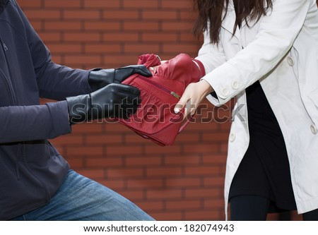A thief yanking a red bag from a woman in front of a brick wall - stock photo