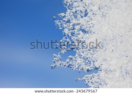 A thin plate of ice on the background of blue sky - stock photo